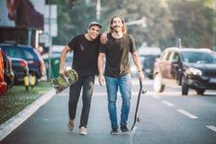 Pro cavalier de la planche à roulettes deux descendant la rue tenant le skatebo image stock