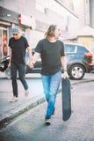 Pro cavalier de la planche à roulettes deux descendant la rue tenant le skatebo photographie stock