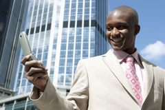 Pro with Cell. Successful businessman using a cellular phone in the city royalty free stock photo
