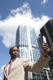 Pro with Cell. Businessman holding a cell phone while standing in the financial district Stock Photos