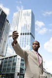 Pro with Cell. Businessman holding a cell phone while standing in the financial district Royalty Free Stock Image