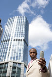 Pro with Cell. Businessman holding a cell phone while standing in the financial district Stock Photography