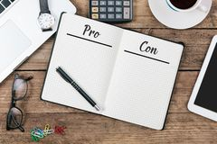 Pro and Con lists in note pad on office flat lay royalty free stock photo