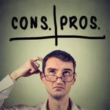 Pro - e - contro, pro e contro il concetto di discussione Uomo con i vetri che cerca decidente Fotografia Stock