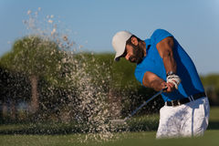 Pro golfer hitting a sand bunker shot. Pro golf player shot ball from sand bunker at course Royalty Free Stock Photography