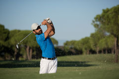 Pro golfer hitting a sand bunker shot. Pro golf player shot ball from sand bunker at course Stock Photography