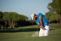 Pro golfer hitting a sand bunker shot. Pro golf player shot ball from sand bunker at course Stock Photo