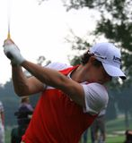 Pro golfer Rory McIlroy. Watches his ball before hit with the iron club Royalty Free Stock Images