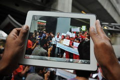 Pro-Government 'Red Shirt' Protest in Bangkok. A protester uses a tablet computer to photograph a Red Shirts rally in Bangkok's shopping district, where Stock Photo