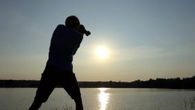 Pro mężczyzna strzela prześwietnego sunpath na jeziorze przy zmierzchem w mo zbiory wideo