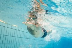 Pro male swimmer in the swimming lane. Male swimmer in the swimming pool.Underwater photo with copy space Royalty Free Stock Images
