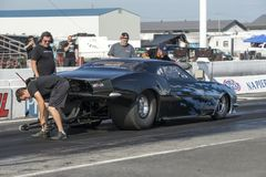 Pro mod drag car at the starting line. Picture of pro mod drag car with crew members in preparation at the starting line on the track during the john scotti all Royalty Free Stock Photos