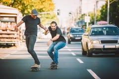Pro patim do passeio do cavaleiro do skate dois através dos carros na rua fotografia de stock royalty free