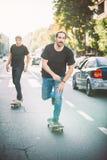 Pro patin de tour de cavalier de la planche à roulettes deux par des voitures sur la rue Photos libres de droits