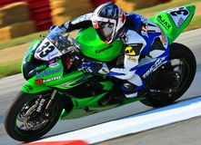 Pro super motorcycle. Racing Kawasaki motorcycle makes the tight corner on the paved race track stock image