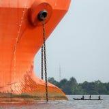 Proa de una nave grande cara a cara con una pequeña piragua de madera Foto de archivo libre de regalías