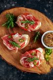 Proaciutto ham, Italian bruschetta appetizers with soft chees, onions, whole grain mustard, chillies and fresh rosmary. Royalty Free Stock Image