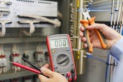 Probador y cortaalambres en manos del electricista contra el panel de control eléctrico del equipo de la automatización Imagen de archivo