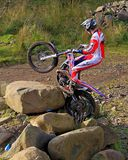 Probemotorrad Wheelie über Felsen Stockfotos