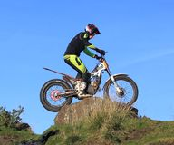 Probemotorradfahrer, der auf Fahrrad auf Felsenschattenbild gegen blauen Himmel steht Stockfotografie