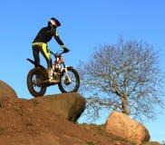 Probemotorradfahrer, der auf Fahrradschattenbild gegen blauen Himmel steht Lizenzfreie Stockfotos