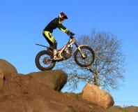 Probemotorradfahrer, der auf Fahrradschattenbild gegen blauen Himmel steht Lizenzfreies Stockfoto