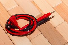 Probes of a digital multimeter on the floor of wooden planks stock photography