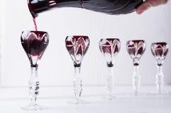 Probieren des alkoholischen Getränks Strömender roter Alkohol in Weinlesegläser lizenzfreie stockfotografie