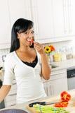 Probierengemüse der jungen Frau in der Küche Stockfotos