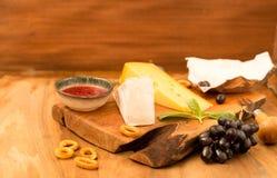 Probierenkäseteller mit Kräutern und Früchten auf Holztisch Lebensmittel für Wein und romantisches, Käsedelikatessen Stockfotos