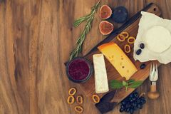 Probierenkäseteller mit Kräutern und Früchten auf Holztisch Lebensmittel für Wein und romantisches, Käsedelikatessen Beschneidung Lizenzfreie Stockbilder