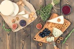 Probierenkäseteller mit Kräutern und Früchten auf Holztisch Lebensmittel für Wein und romantisches, Käsedelikatessen Beschneidung Lizenzfreie Stockfotografie