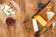 Probierenkäseteller mit Kräutern und Früchten auf Holztisch Lebensmittel für Wein und romantisches, Käsedelikatessen Hintergrund  Stockfoto