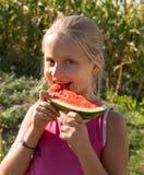 Probierenwassermelone des kleinen Mädchens Lizenzfreies Stockbild