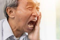 Problème dentaire d'aîné de dent sérieuse asiatique de douleur images stock