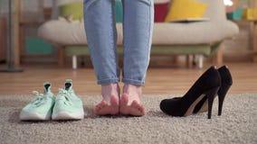 Probleem om een vrouw te kiezen wat tussen tennisschoenen en schoenen met hielen te dragen stock footage