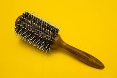 The problem of baldness, dropped hair on the comb on a yellow background.  stock photo