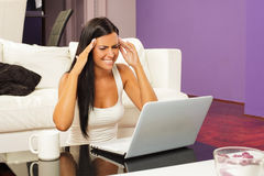 Problem. Beautiful woman sitting on armchair with laptop Stock Photo
