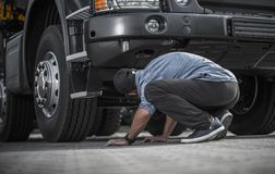 Problem with Broken Truck. Caucasian Trucker in His 30s Looking For Damages Under His Vehicle. Automotive and Transportation Industry Theme Royalty Free Stock Image