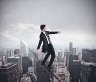 Problem in business. Businessman is balancing on a rope over a city vector illustration