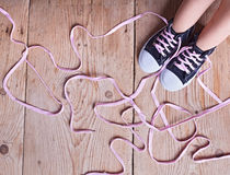 The problem - child feet and shoelaces. The shoe tie puzzle - child feet and long twisted shoelaces on wooden floor stock photo