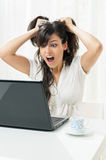 Problem with computer. Young woman has problems with her laptop and pulls the hairs Royalty Free Stock Image
