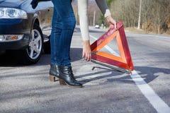 Problem der jungen Frau mit dem Auto auf der Straße Stockfotografie