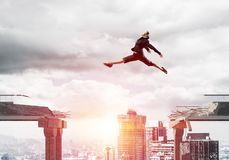 Problem and difficulties overcoming concept. Business woman jumping over gap in concrete bridge as symbol of overcoming challenges. Sunlight and cityscape on Royalty Free Stock Image