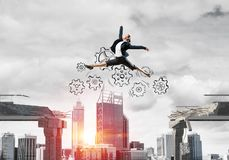 Problem and difficulties overcoming concept. Business woman jumping over gap with gear mechanism in concrete bridge as symbol of overcoming challenges Royalty Free Stock Image