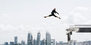 Problem and difficulties overcoming concept. Business woman jumping over huge gap in concrete bridge as symbol of overcoming challenges. Cityscape on background Royalty Free Stock Photos