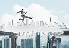 Problem and difficulties overcoming concept. Businessman jumping over gap in concrete bridge as symbol of overcoming challenges. Cityscape on background. 3D Stock Images