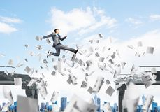 Problem and difficulties overcoming concept. Businessman jumping over gap with flying paper documents in concrete bridge as symbol of overcoming challenges Royalty Free Stock Photos