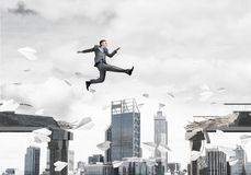 Problem and difficulties overcoming concept. Businessman jumping over gap with flying paper planes in concrete bridge as symbol of overcoming challenges Royalty Free Stock Photo