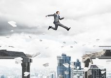 Problem and difficulties overcoming concept. Businessman jumping over gap with flying paper planes in concrete bridge as symbol of overcoming challenges Stock Image